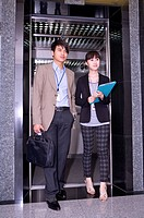 Young man and woman walking out of elevator together