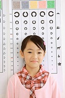 Little girl standing before eye chart and smiling