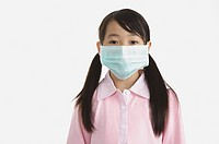 Little girl wearing a surgical mask and looking at the camera (thumbnail)
