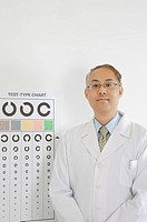 Doctor standing before eye chart and looking at the camera (thumbnail)
