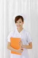 Young nurse holding document folder and smiling at the camera (thumbnail)