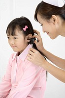 Young nurse checking little girl's ear with medical equipment