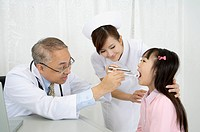 Doctor and nurse checking little girl's mouth