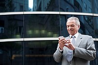 Senior Businessman holding mobile phone in front of an office building
