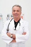 Senior doctor standing with arms crossed and smiling at the camera