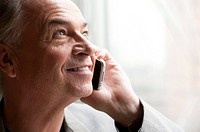 Senior businessman holding mobile phone and looking up with smile