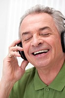 Senior_aged man listening to music with eyes closed and laughing