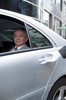 Senior businessman sitting in the car and looking at the camera with smile
