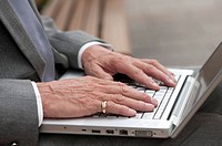 Senior businessman, Close_up of human hands using laptop