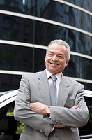 Senior businessman standing with arms crossed and smiling in front of an office building