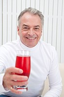 Domestic Life, a senior man holding a glass of drink and smiling at the camera