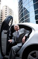 Senior businessman getting off the car