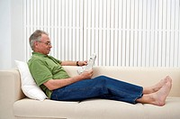 Domestic Life, a senior man sitting on the sofa and reading newspaper