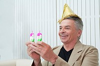 Domestic Life, a senior man holding birthday candles and smiling happily
