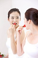 Beauty Treatment, Woman looking at the mirror and eating a strawberry