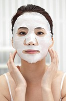 Beauty Treatment, Woman putting facial mask on her face and looking at the camera