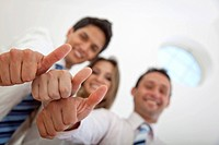 Business people with their thumbs up indoors