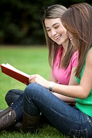 Girls studying with a notebook outdoors and smiling