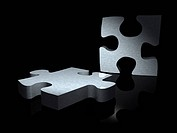 couple of metal puzzle pieces over a black background