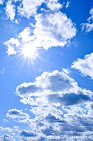 Background of blue sky with shining sun and clouds