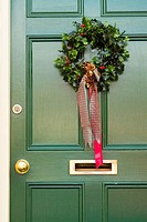 Christmas holly wreath on green door