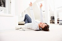 Young woman listening music lying on floor.