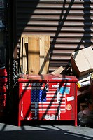 A red garbage dumpster with American flag stands on pavement covered with shadows cast by staircase