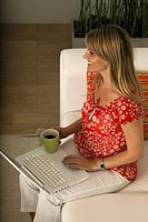 Woman relaxing at home with cup of coffee, using laptop computer