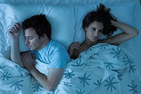 Couple lying together in bed, woman restlessly awake looking away