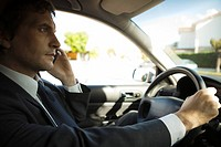 Businessman using cell phone while driving (thumbnail)