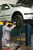 Mechanic changing tires of car elevated on hydraulic lift