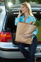 Woman sitting in open hatchback with bag of groceries on lap making phone call
