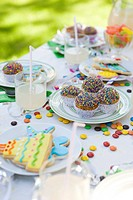 Iced cookies and cupcakes on table decorated with streamers and candy