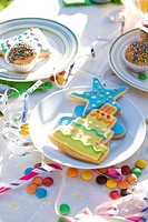 Iced cookies, cupcakes on table decorated with streamers and candy