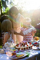Girl opening gift at outdoor birthday party