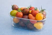Assorted cherry and plum tomatoes in plastic container