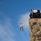 Businessman jumping off cliff while co_workers watch
