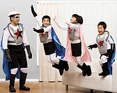 Korean children in superhero costumes jumping off sofa