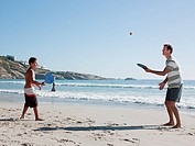 Father and son on playing paddleball on beach
