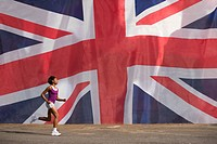 Woman running past british flag