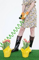 Woman with hose and flowers on artificial turf