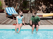 Boy and girl on edge of swimming pool