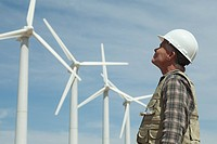 Man in hard hat looking at wind turbines