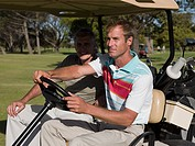 Two mature men in golf cart on golf course