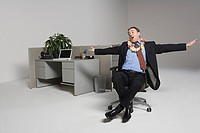 Businessman messing around on office chair