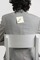 Businessman with adhesive note stuck to his back