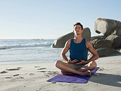 Young man doing yoga on beach