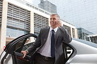 Businessman on cellphone getting out of car