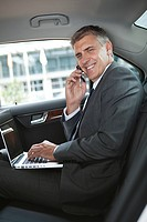 Businessman in car with cellphone and laptop