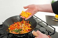 Man stir frying vegetables